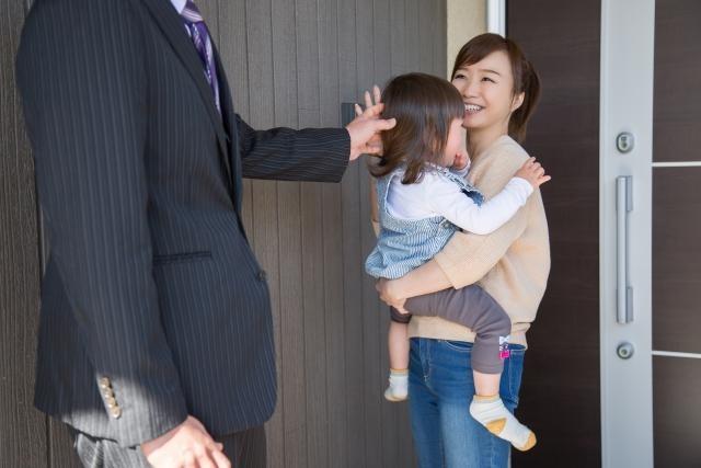 赤ちゃんを抱っこしている女性とスーツ姿の人
