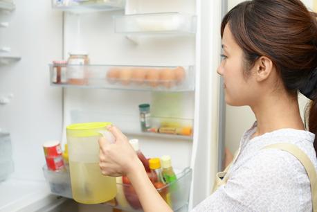 冷蔵庫に飲み物をしまう女性