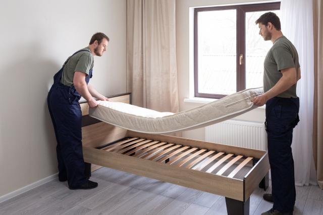 ベッドを運んでいる二人の男性