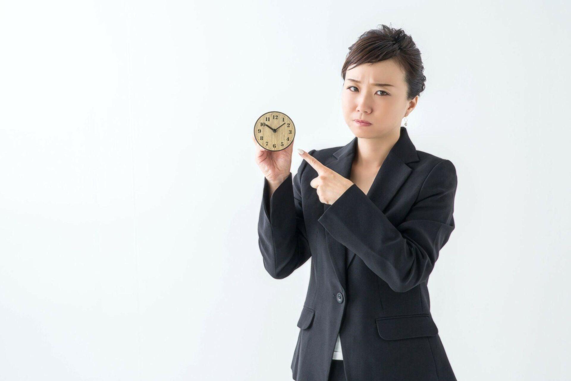 時計を指さしている女性