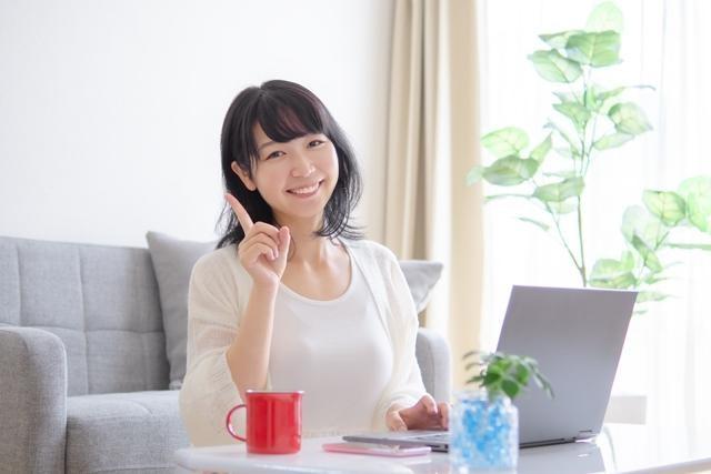 パソコンの前で人差し指を立てている女性